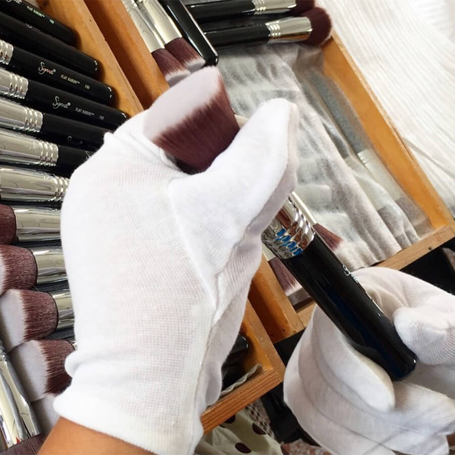 White gloved hand holding F80 brush